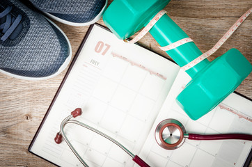 Open calendar and dumbbell with stethoscope.