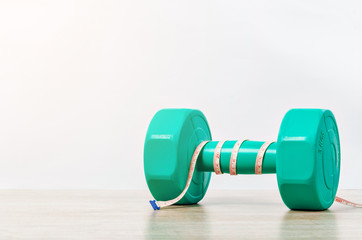 Green dumbbell and measuring tape on wooden background.