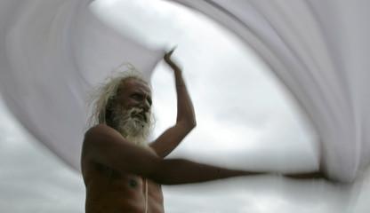A HINDU HOLY MAN DRIES HIS ROBE AT THE KUMBH MELA IN NASIK.