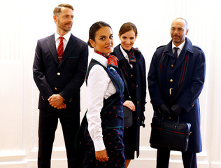 An Alitalia airline crew member displays her new uniform during the official presentation of Alitalia's new Alberta Ferretti-designed uniforms in Milan