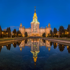 Night view of the main building of the Moscow State University from the point of view on the Vorobyovy hills in the summer. Beautiful reflections of a lighted building in a fountain with night sky.