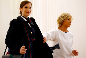Italian designer Alberta Ferretti shows the details of an overcoat during the official presentation of Alitalia's new Alberta Ferretti-designed uniforms in Milan