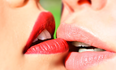 Lesbian love. Lipstick kiss, homosexual love. Two girls close up mouth to mouth. Female mouths in a kiss, sex between women. Young girls and pink lipstick. Beautiful sensual lips. Sexy girl
