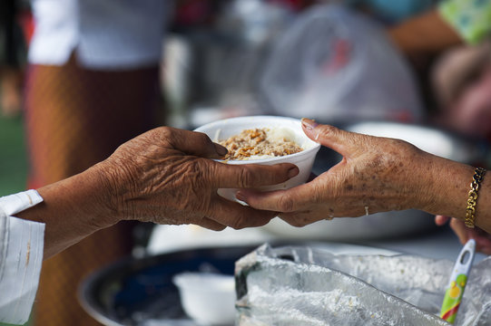 Rich people give food to the poor. starvation concept