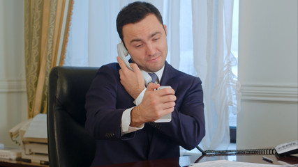 Successful businessman taking a funny selfies by his smartphone and then having a landline phone call