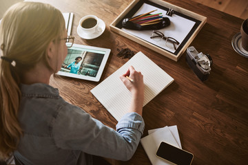 Woman writing down notes and working online at home