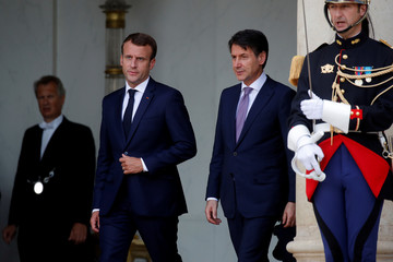 French President Emmanuel Macron accompanies Italian Prime Minister Giuseppe Conte after a meeting at the Elysee Palace in Paris