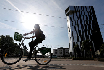 A cyclist rides his bike in front of the Elithis-Danube tower in Strasbourg
