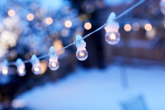 String of glowing party lights outdoors in winter