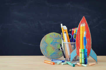 Back to school concept. rocket, earth globe and pencils in front of classroom blackboard.