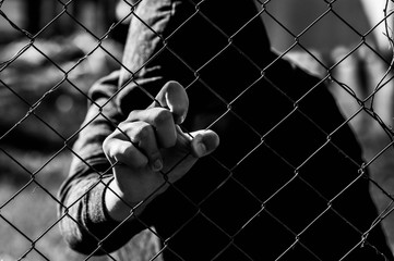 Young unidentifiable teenage boy holding the wired garden at the correctional institute in black and white, conceptual image of juvenile delinquency, focus on the boys hand. - fototapety na wymiar