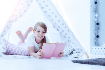 Time for a new adventure. Cute preteen girl smiling while relaxing in a teepee and reading a fairytale during a weekend at home.