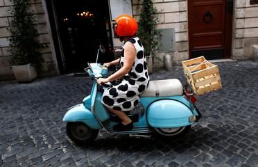 A woman drives a Vespa scooter in downtown Rome