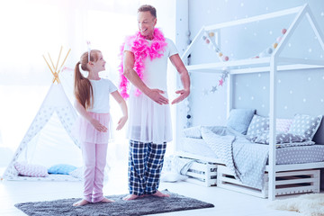 Love her to the moon and back. Thoughtful mature man pretending to be ballerina while wearing a feather boa and playing with his daughter at home.