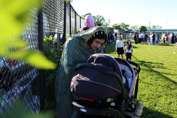 A Muslim woman attends to a child during Eid Al-Fitr prayers at Bensonhurst Park to mark the end of Ramadan in the Brooklyn borough of New York City