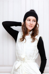 Hipster Style Brunette Girl Swag wearing Black fashion beanie knitted hat with bumbon pumpon. Season Fall Winter