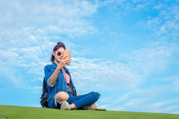 Asain woman take a picture of herself with a smartphone on blue sky and white clouds background.