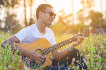 Man playing guitar on a sunny day.