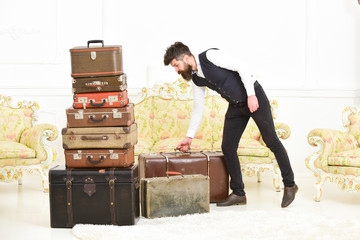 Macho elegant on strict face carries vintage suitcase. Man, butler with beard and mustache wearing classic suit delivers luggage, luxury white interior background. Luggage and relocation concept.