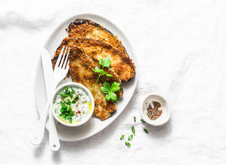 Eggplant schnitzel and greek yogurt, greens sauce on a light background, top view. Tasty snack, tapas