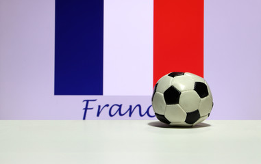 Small football on the white floor and Tri Color or blue white and red color of French nation flag background with France text. The concept of sport.