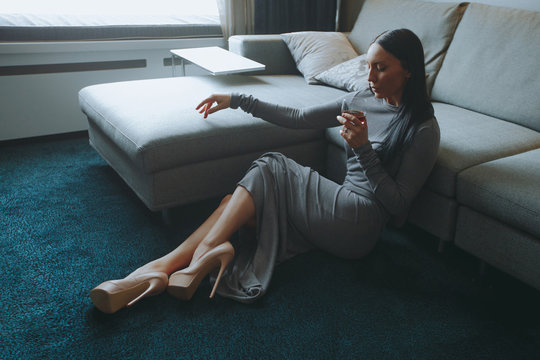 Luxurious young brunette sitting on floor in living room with glass of whiskey