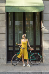 Woman standing with vintage bicycle on street