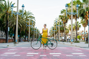 Female standing on road with bicycle Fotomurales