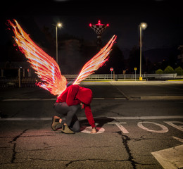 Fallen male angel kneeling in city parking lot, with fire wings spreading from his back. Unrecognizable young man