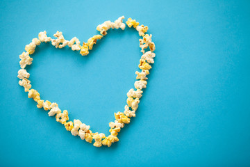 Food. Image of the Heart Forms from Popcorn. Delicious Popcorn on Blue Background. Cinema.