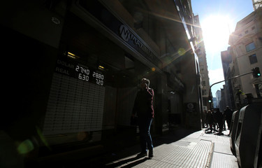 A pedestrian walks past an electronic board showing currency exchange rates in Buenos Aires' financial district