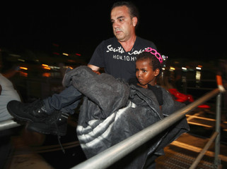 An immigration police officer carries a would-be immigrant child off an Armed Forces of Malta Maritime Squadron patrol boat after arriving at the AFM base at Haywharf in Valletta's Marsamxett Harbour