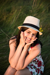 Positive girl in dress in flower print and hat.