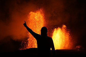 Victory pose in front of a lava fountain of the volcanic eruption of Kilauea in Hawaii