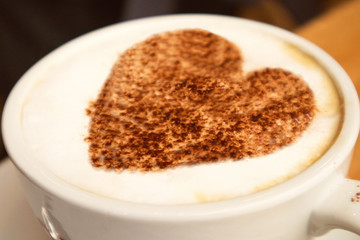 closeup of a big white cup of hot coffee cappuccino with art design heart on it  standing on a wooden background,love concept