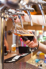 The barman pours beer from the tap