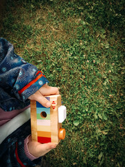 a little girl in a summer Park with a toy wooden camera in his hands playing on the grass