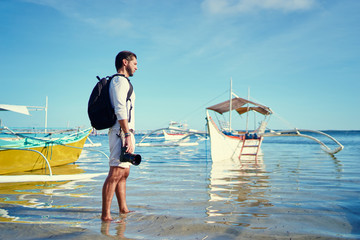 Photography and travel. Young man with rucksack holding camera walking on fishing beach enjoying beautiful tropical sea view.