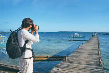 Photography and travel. Young man with rucksack standing on wooden fishing pier taking photo of beautiful tropical sea view.
