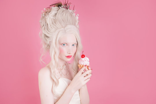 A blond woman with a beautiful luxurious rococo hair style in a white dress on a pink background. Girl with a cake with a cherry in hand