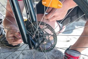 Man repairing a bicycle, preparing for the season, bicycle wheel