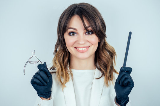 young attractive manicurist professional (master of manicure) woman in a white jacket and black rubber gloves is holds tools for removing cuticles and a nail file in a beauty spa salon