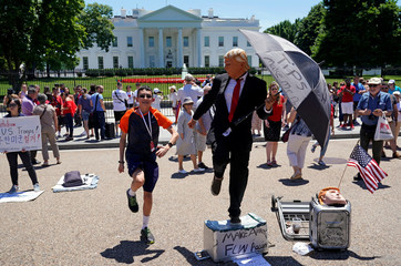 A boy dances along with a street performer dressed as U.S. President Donald Trump in Washington