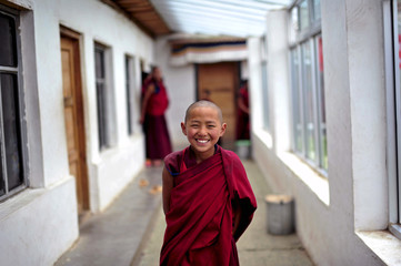 A young Tibetan monk laughs as he waits for a free medical examination at a hospital in Henan Autonomous County