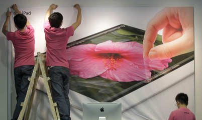 Employees hang a poster advertising the New iPad at an Apple dealership in Wuhan