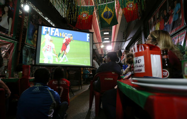 Fans watch the World Cup soccer match between Spain and Portugal at the Municipal Market of foodsin Rio de Janeiro