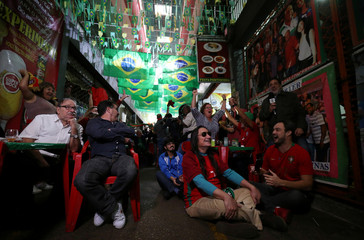 Fans celebrate a goal during the World Cup soccer match between Spain and Portugal at the Municipal Market of foods in Rio de Janeiro