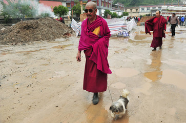 A Tibetan monk walks with his dog outside a monastery in Xining