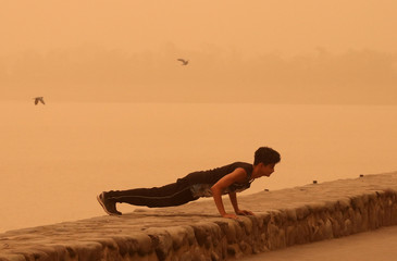 A man exercises amidst haze and dust near Sukhna lake in Chandigarh