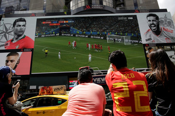 People watch the World Cup Group B - Portugal vs Spain soccer match at Times Square in New York City, New York